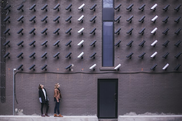 Picture of people looking at dozens of security cameras mounted on a wall